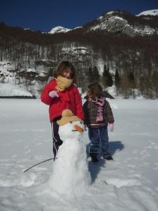 Rachele, Greta e il pupazzo di neve (e sullo sfondo il Rifugio Policreti)