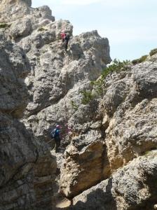 Guida alpina con due escursionisti. Assicurati anche con corda.