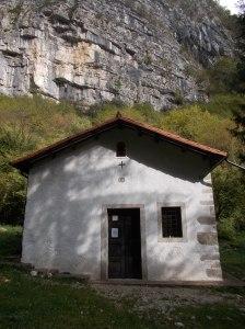 Chiesetta di San Tomè. Sullo sfondo il paretone della falesia di Dardago